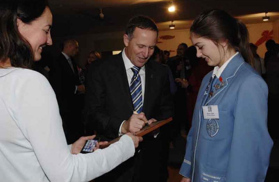 Prime Minister John Key autographs a certificate for Frances Fulton of St Hilda's Collegiate...