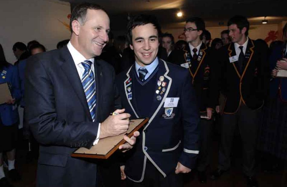 Prime Minister John Key autographs a certificate for Caleb Gray of King's High School.
