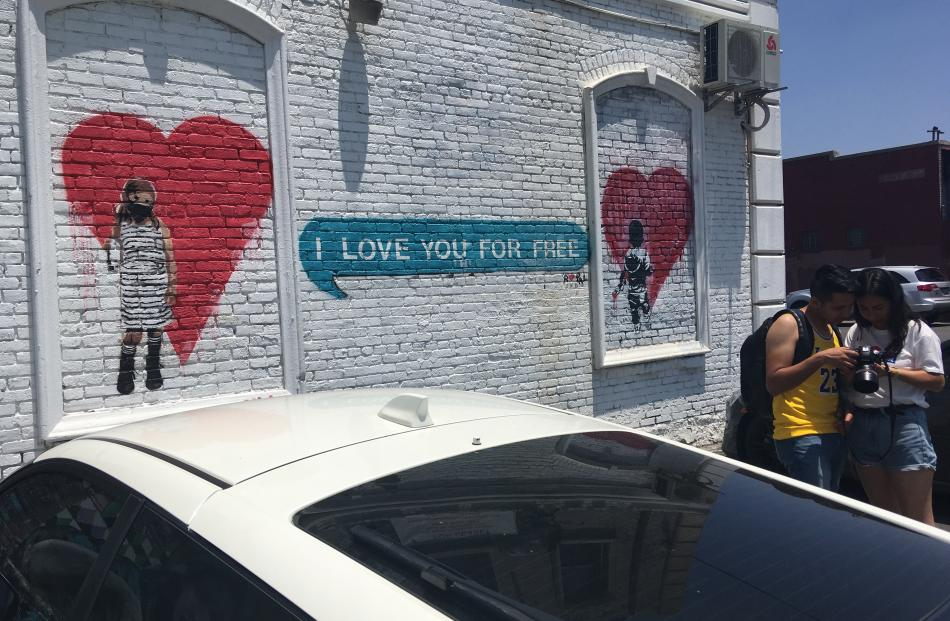 """A couple inspect a """"selfie"""" taken outside a street art mural in downtown LA's arts district...."""