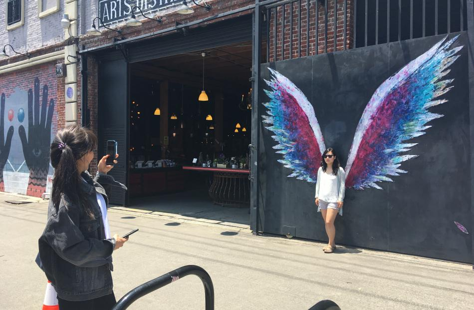 A visitor is photographed between artist Colette Miller's angel wings in downtown Los Angeles'...
