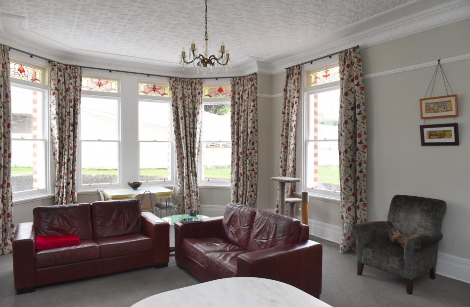 The family room features an original pressed metal ceiling and stained glass windows.