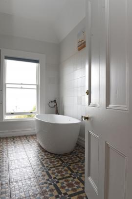 The bathtub in the original bathroom offers views of the city and the coastline.