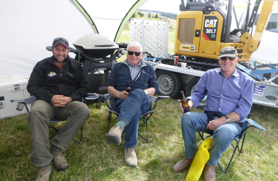 Finding shelter from the westerly wind while enjoying a cold beverage are (from left) Nick Terry,...