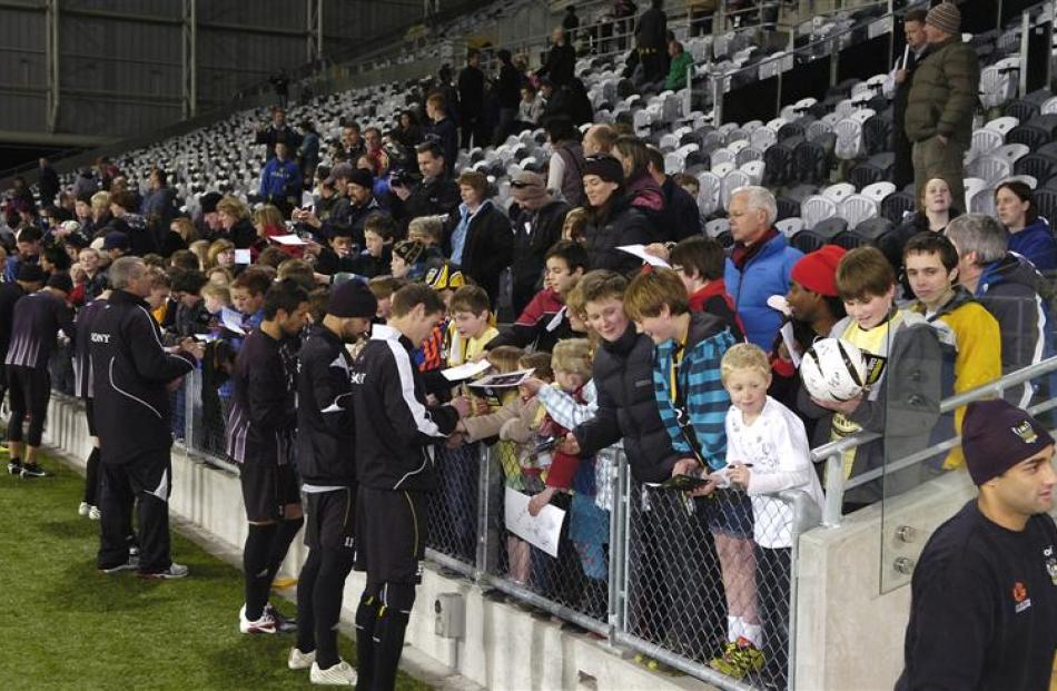 Fans throng the pitch sideline at the stadium to get Phoenix team members' signatures.