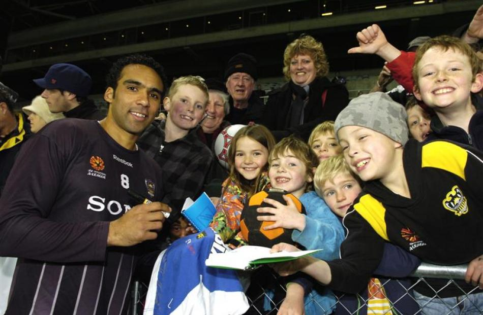 Wellington Phoenix player Paul Ifill signs autographs for fans at a team training session at the...