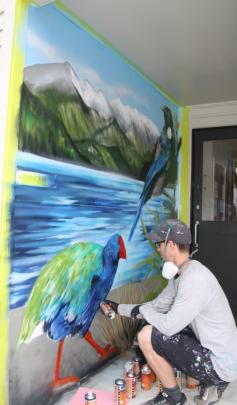 Guest artist and Guest Judge Danny (Deow) Owen working on the mural to the entrance to the...