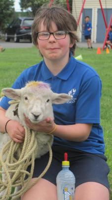 Kate Cochrane (10) with Molly, the winner of the lamb drinking competition.