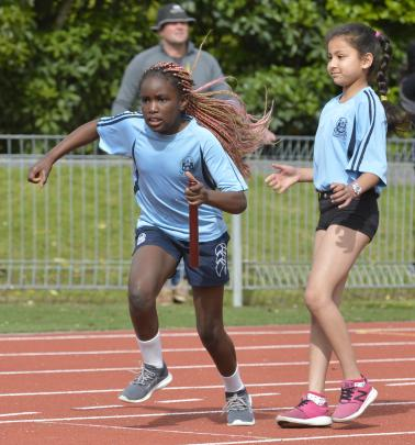 Esther Koudayah takes the baton from St Joseph's Cathedral School team-mate Muskan Uniyal in an...