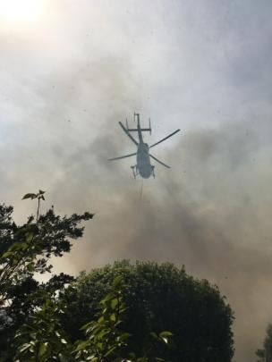A rescue helicopter, obscured by smoke, fights the blaze with a monsoon bucket. Photo: Supplied