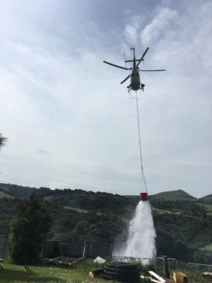 A rescue helicopter fights the blaze with a monsoon bucket. Photo: Supplied