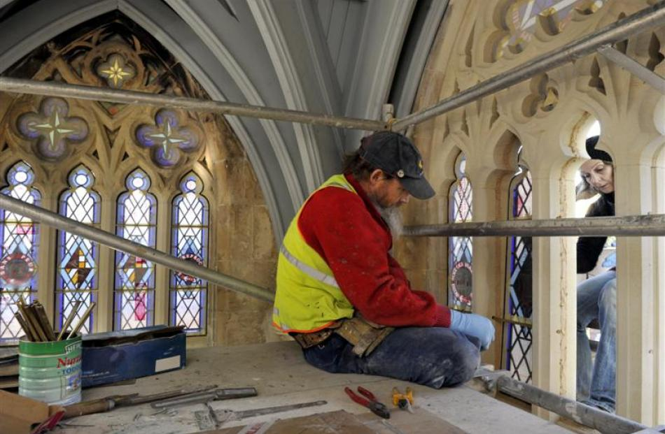 Stained-glass artist Peter Mackenzie, assisted by Suzanne O'Sullivan, fits one of the stained...