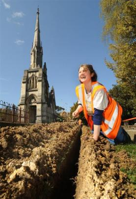 Archaeologist Sheryl McPherson inspects a trench being dug to carry cables for a new security and...