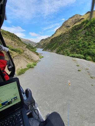A helicopter crew surveys the flooded Shotover River. Photo: ORC