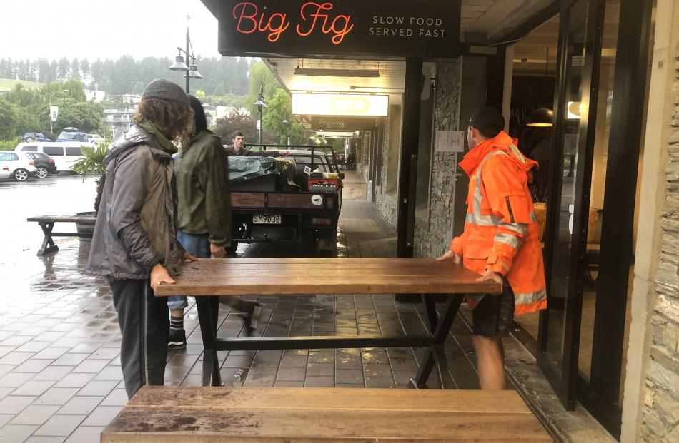 Volunteers move The Big Fig restaurant outdoor seating after the contents of the restaurant had been packed and moved out overnight. Photo: Kerrie Waterworth