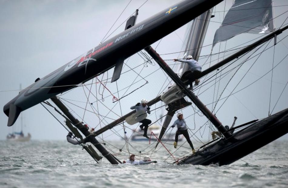 Team Artemis from Sweden right themselves after capsizing during the final fleet race of the...