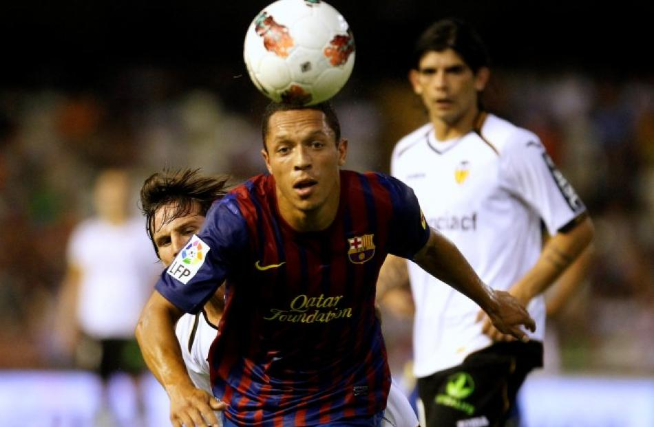 Barcelona's Adriano heads the ball past Valencia's Pablo Piatti and Ever Banega (R) during their...