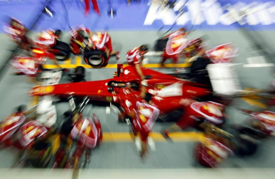 Ferrari crew conduct a pit stop practice at the Marina Bay street circuit ahead of the Singapore...