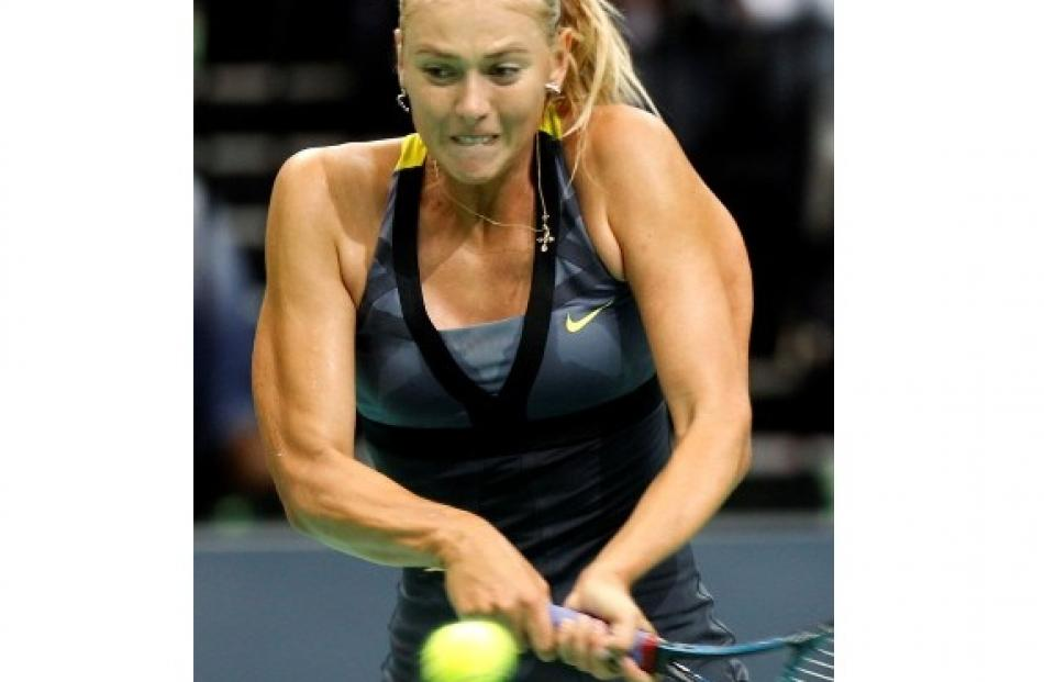Maria Sharapova of Russia returns a shot to compatriot Vera Zvonareva during their exhibition...