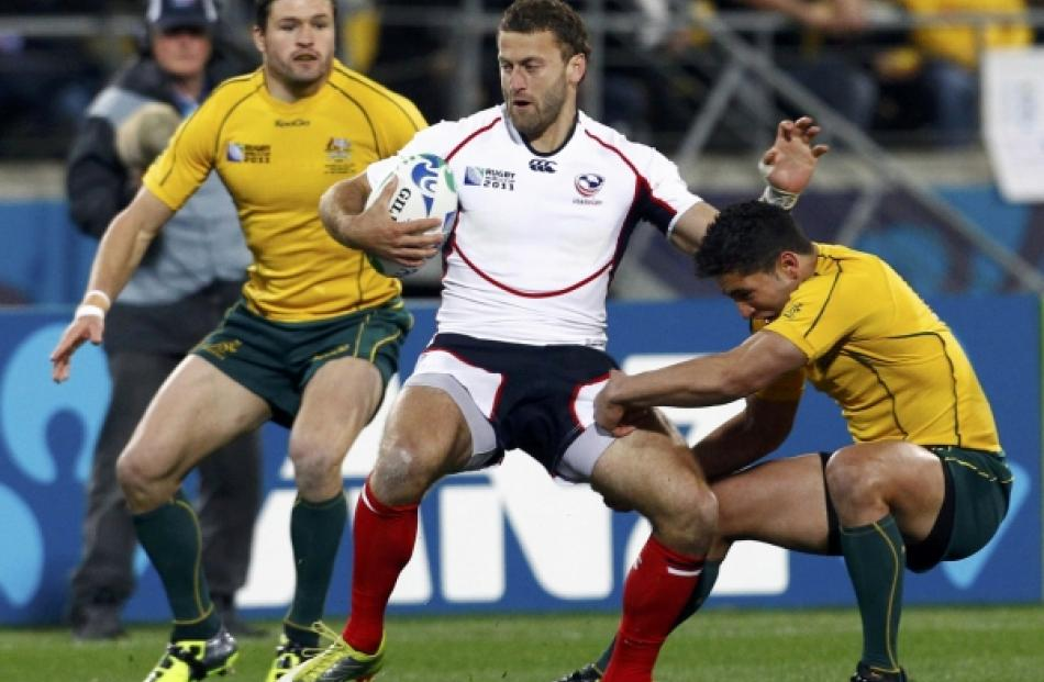 Australia Wallabies' Anthony Fainga'a (right) tackles Kevin Swiryn (centre) of the US as Adam...