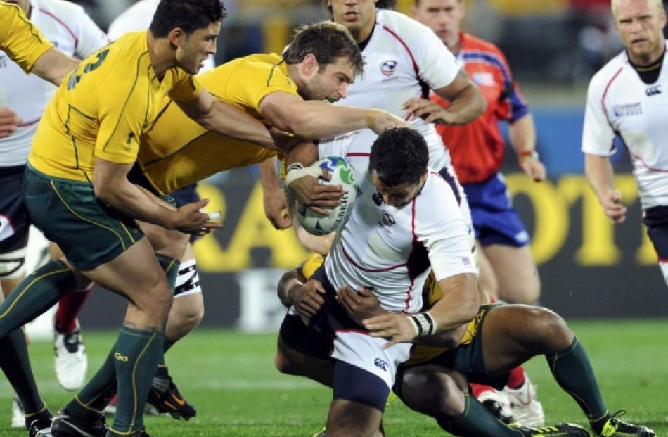 Australia Wallabies captain Will Genia (hidden) tackles Colin Hawley of the US during their Rugby...