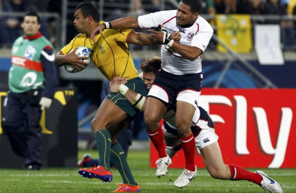Blaine Scully (back) and Tai Enosa of the US tackle Australia Wallabies' Kurtley Beale during...
