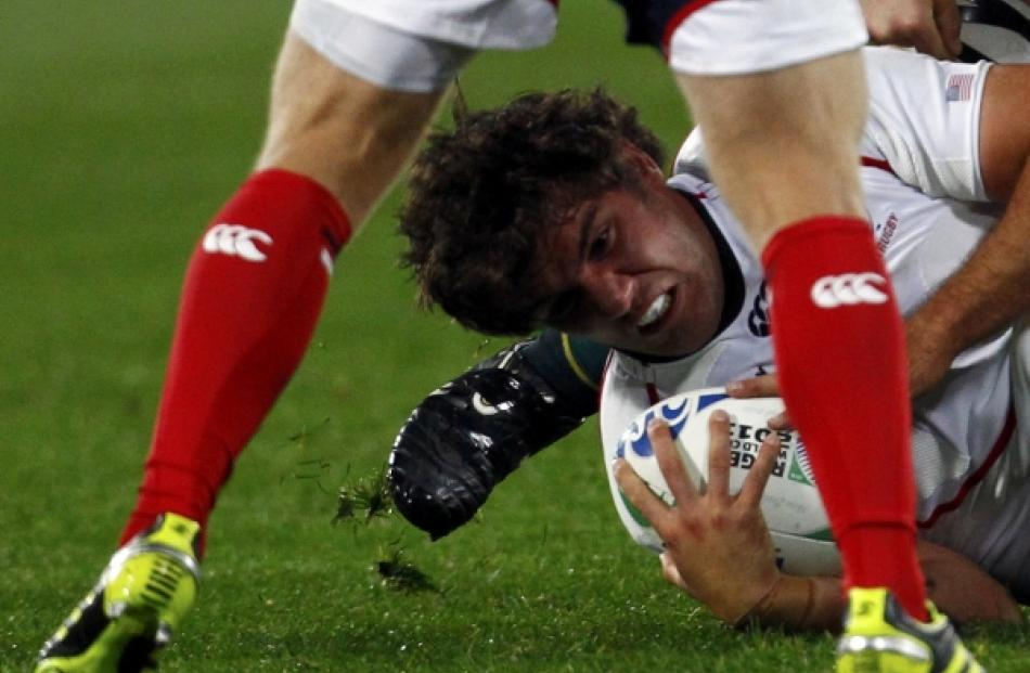 JJ Gagiano of the US moves the ball out as he is tackled during their Rugby World Cup Pool C...