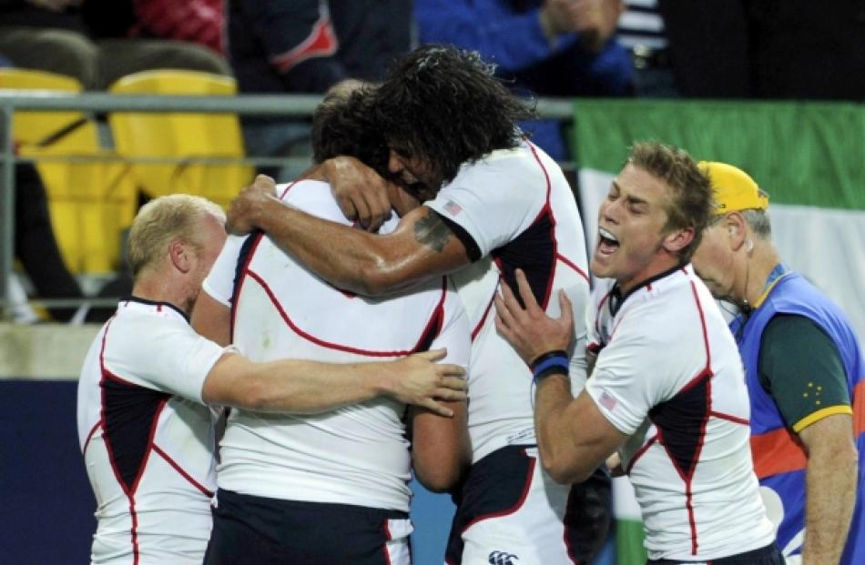 JJ Gagiano (second from left) of the US celebrates scoring a try with teammates during their...