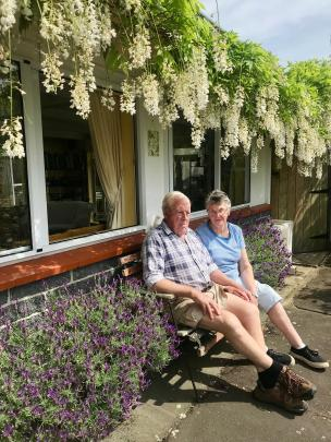 Myra and Richard Wells, of Abbotsford, under their white wisteria. Photo: Gillian Vine