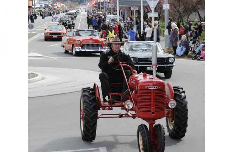 Alan McCrostie leads a parade of classic cars down Centennial Avenue.