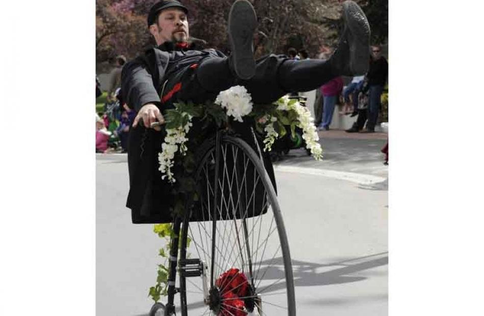 Shane Price glides down Centennial Avenue on his Penny Farthing.