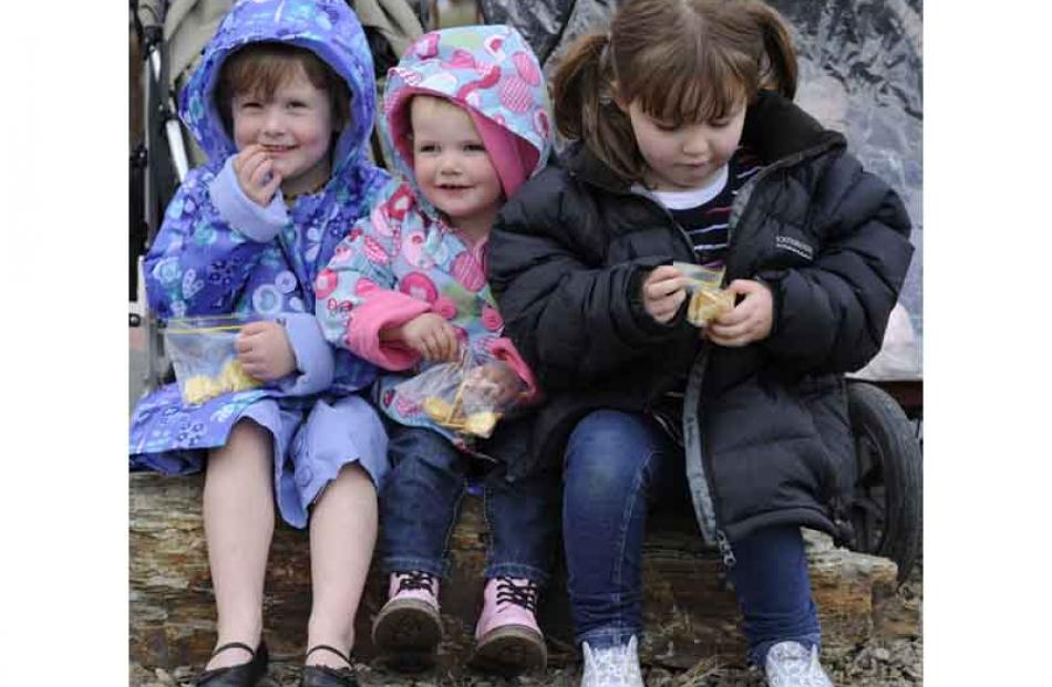 Tucking into snacks before the procession are from left Brydee (3) and Camryn Patrick (2)  of...