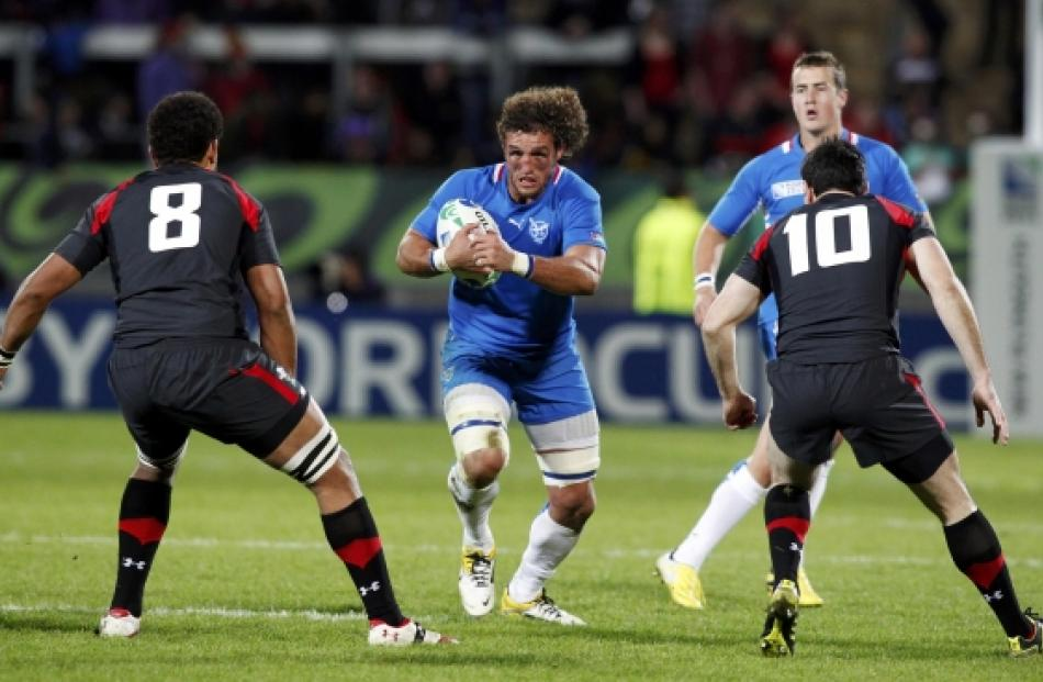 Namibia captain Jacques Burger runs towards Wales' Toby Faletau (left) and Stephen Jones (R)...