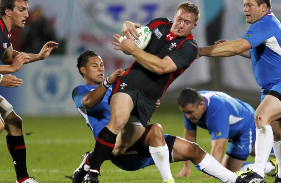 Namibia's Darryl De La Harpe tackles Wales' Lloyd Burns (centre) during their Rugby World Cup...