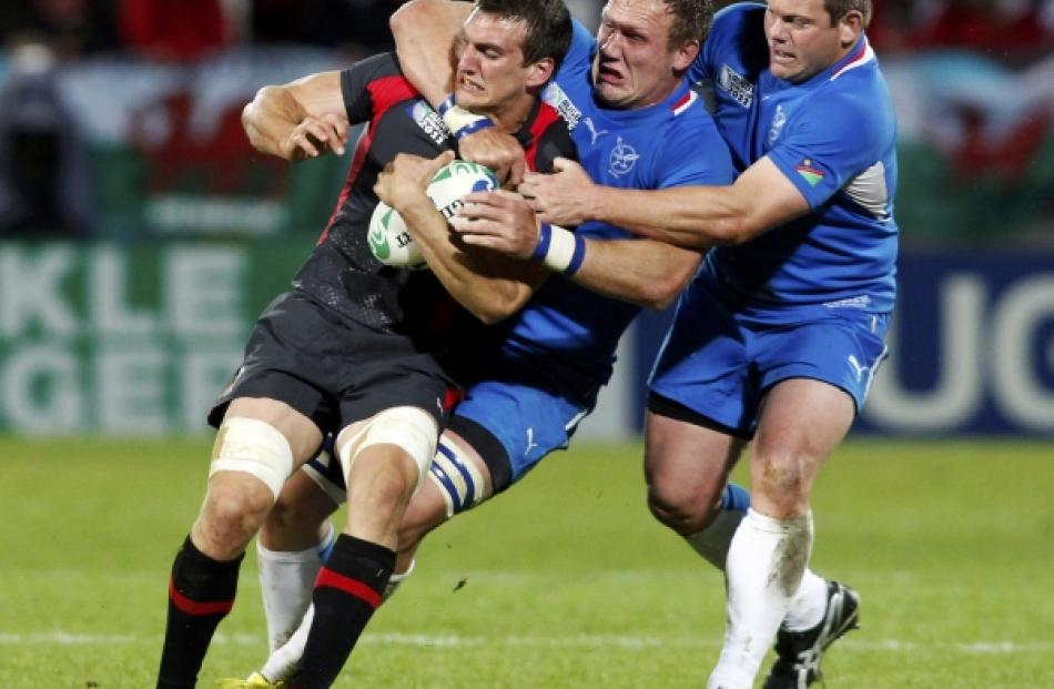 Namibia's Heinz Koll (centre) and Hugo Horn tackle Wales captain Sam Warburton (L) during their...
