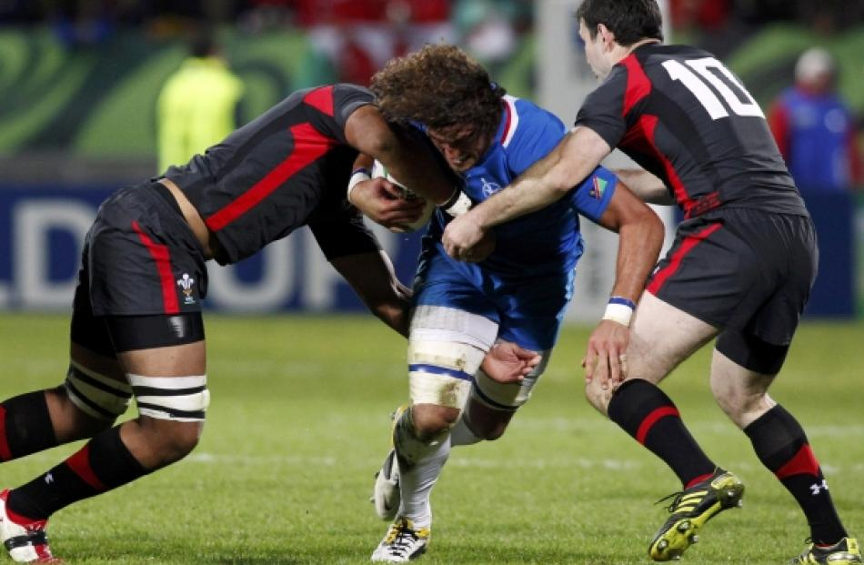 Wales' Toby Faletau (left) and Stephen Jones tackles Namibia captain Jacques Burger (centre)...
