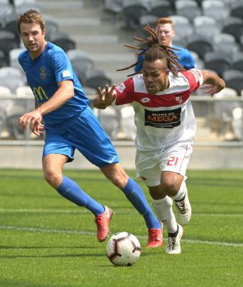 Waitakere United's Andrew Abba keeps his eye on the ball as Southern United players Erik Panzer ...