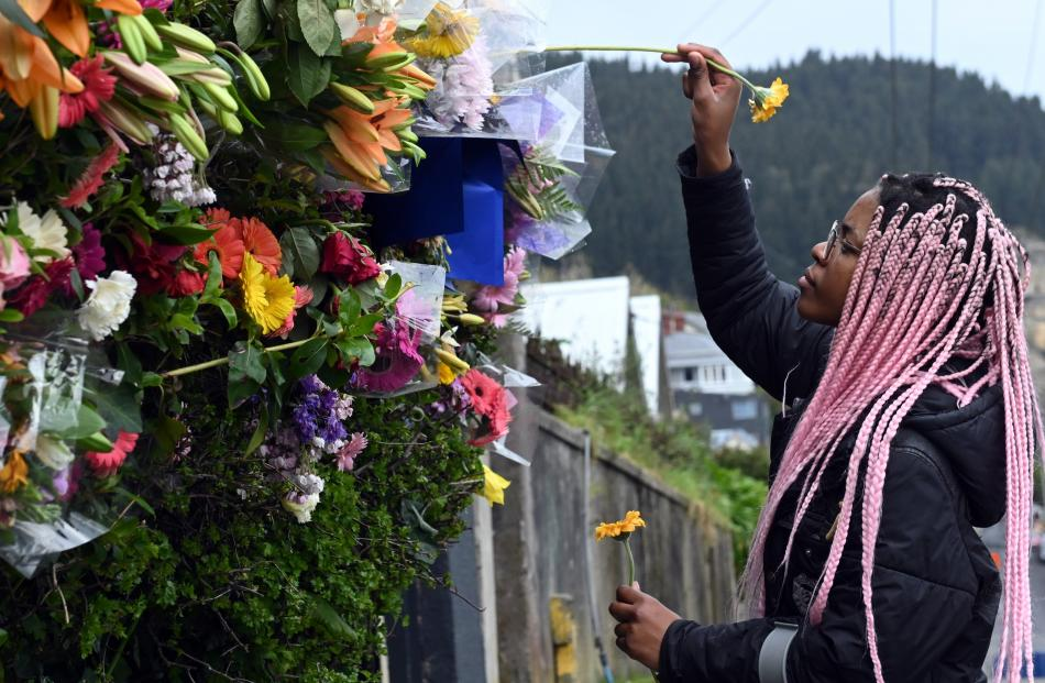 Tasha Gweshe, a student from a neighbouring flat, places flowers in the hedge of a flat known as ...