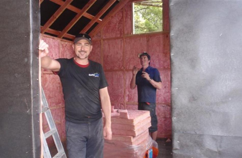 Paradise Trust co-manager Daman Groshinski (left) and Mike Kingan, of Wanaka, install insulation...