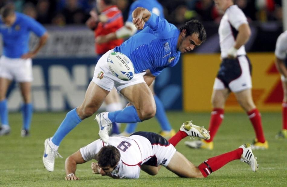 Italy's Gonzalo Canale jumps over Mike Petri (on ground) of the US as he fumbles the ball during...