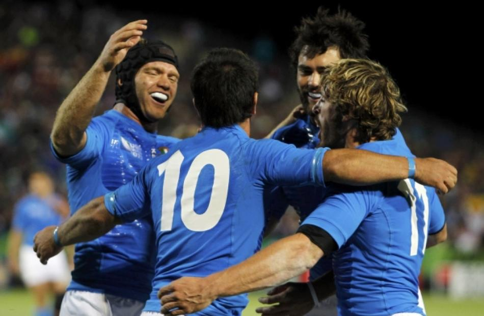 Italy's Luciano Orquera (10) celebrates scoring a try with teammates during their Rugby World Cup...