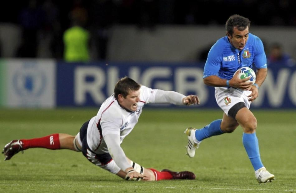 Italy's Luciano Orquera (right) shakes off a tackle by Hayden Smith of the US during their Rugby...