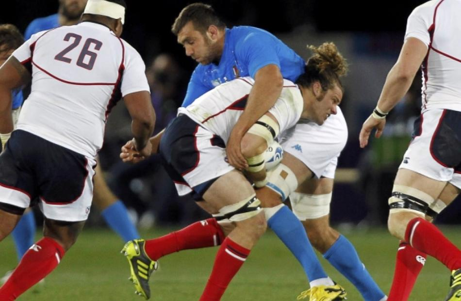 Italy's Quintin Geldenhuys tackles US captain Todd Clever (centre) during their Rugby World Cup...