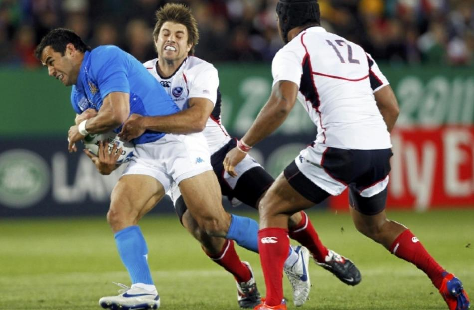 James Paterson (centre) of the US tackles Italy's Gonzalo Canale (left) during their Rugby World...