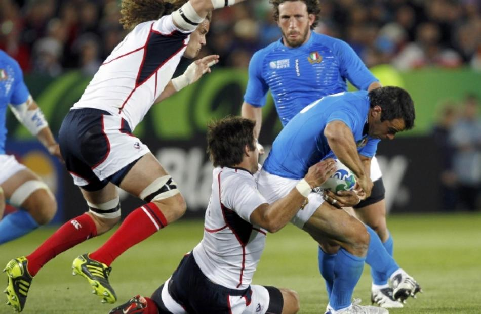 Roland Suniula (centre) of the US tackles Italy's Gonzalo Canale (R) as captain Todd Clever...