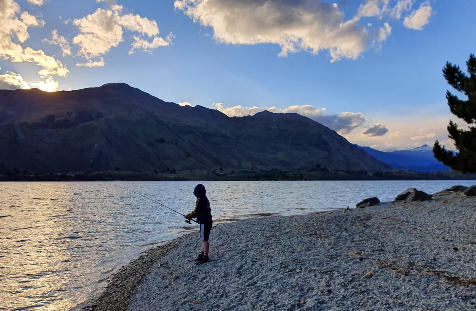 William Evans (10), of Mosgiel, enjoys an evening's fishing in Lake Wanaka. Photo: Katie Evans