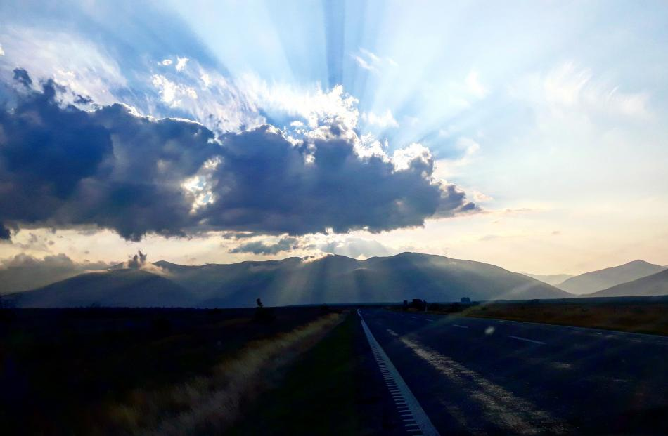 Near Cromwell, en route to Queenstown, evening light breaks through the smoky haze caused by the...
