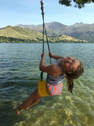 Gretel Calvert (10) enjoys a swing over Lake Hayes on New Year's Eve. Photo: Bushie Calvert