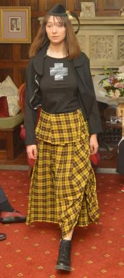 Jessica Clarke  showcases a Dr Margo Barton hat accompanied by a Commes des Garcon yellow tartan...