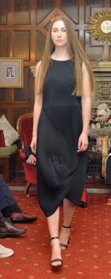 Grace Roseler displays an  Issey Miyake Pleats Please evening dress in black.