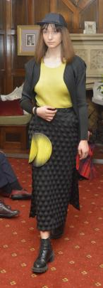 Jessica Clarke  wears Issey Miyake Pleats Please hat, black crop jacket, lime shirt and...